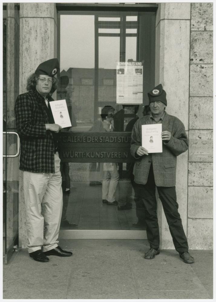 """Horst Brandstätter und Wendelin Niedlich mit Jakobinermützen und der """"stuttgarter documenta"""""""
